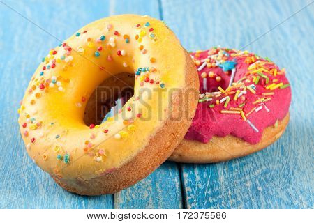two glazed donut on blue wooden background.