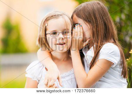 a girl is telling her little sister a secret