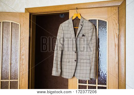 Men's style fashion. Charges groom. Men's jacket hanging on a hanger on the door