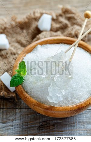 Sticks With Crystal White Sugar In A Wooden Bowl.