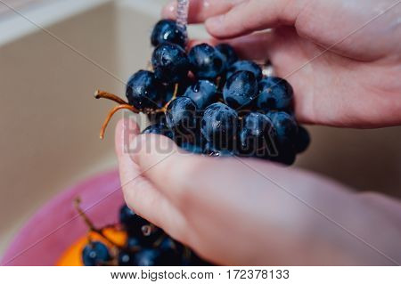 Fresh grapes and oranges submerged in a plate