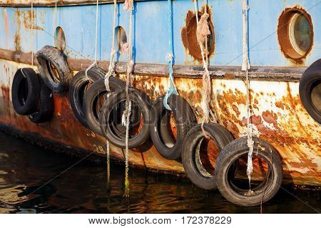 Nesebar Bulgaria - September 10 2014: Old ship Nymph in the port of the old town of Nessebar Bulgaria. Old tires on ship. used for impact protection of a ship. Selective focus.