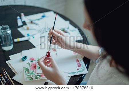 girl painter in white dress draws paints