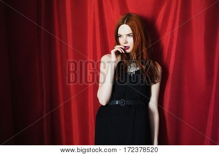 Beautiful red-haired girl in black dress with red lips on red background looking away. Fashion photography. Bright appearance. Red hair. Biting finger
