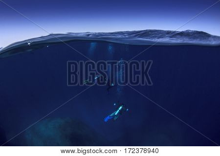 Scuba dive underwater. Sea ocean and sky. Half and half split image (over under)