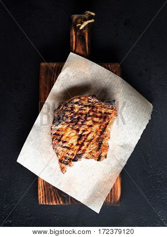 grilled beef on a board on a black background
