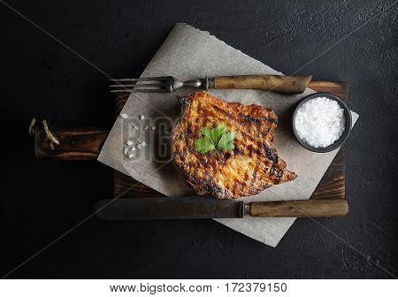 grilled beef on a board, a knife, a fork and salt