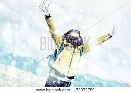 Happy girl enjoying with arms wide open on the snow.