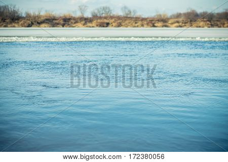 River surface with small ripples in the early spring after the ice drift. Selective focus. Walk on the bank of the Vyatka River, Kirov, Russia.