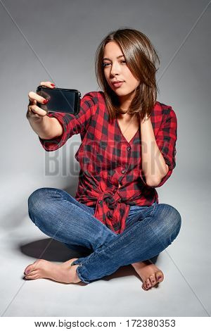 Lovely girl wearing jeans and red checked shirt sitting barefooted at floor making self portrait on her smart phone, studio shot