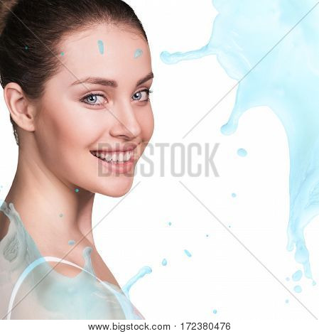 Splashes of water near beautiful face of young woman. Moistening treatment concept.
