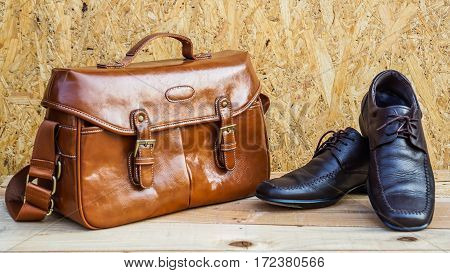 Men's shoes and brown leather bag on wooden floor.