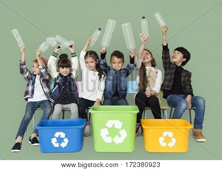Kids and plastic bottles in a recycle bin