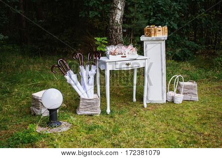 Beautiful unusual wedding decor. Rustic Style. Umbrellas gift boxes baskets with gifts table.