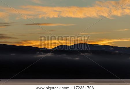 Sunset, nightfall in the Nordic mountains. Lake this side and mountain in the background. Colorful sky, some wind.