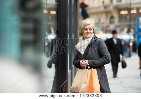 Beautiful senior woman in black coat and woolen scarf window shopping in historical centre of the city of Vienna, Austria. Winter.