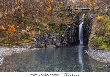 A waterfall deep into a canyon, pond this side. Bridge across the brook, creek and autumn color in the nature.