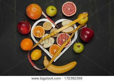 Diet fruits and centimeter on a black background