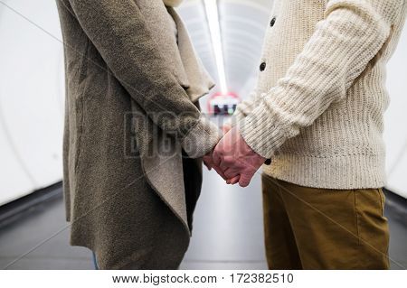 Unrecognizable senior couple in the hallway of subway in Vienna, facing each other, holding hands