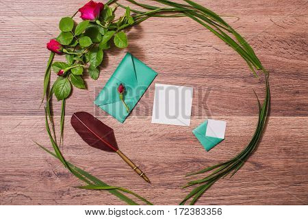 Fountain pen small envelopes white leaf paper frame made of grass and flowers lie on a wooden background. Space for creativity and design. Copyspace flat lay top view.