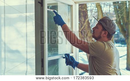 young man is using a rag and squeegee while cleaning windows. professional window cleaner. poster