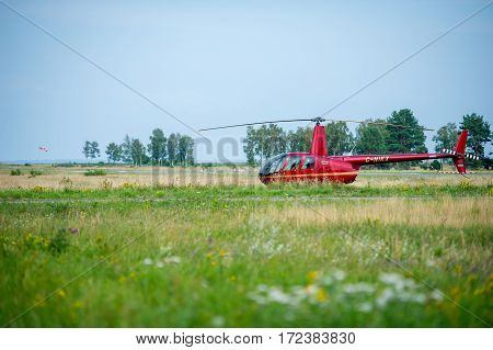 NIDA, LITHUANIA - JULY 24, 2016: Helicopter Robinson R44 in a meadow near Nida airoport.  The Robinson R44 is a four-seat light helicopter produced by the Robinson Helicopter Company since 1992.