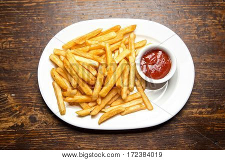 French fries with ketchup sauce in the plate on dark brown wooden table