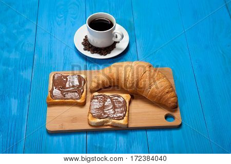 Cup Of Coffee With A Croissant And Toast With Chocolate On A Blue Wooden Table