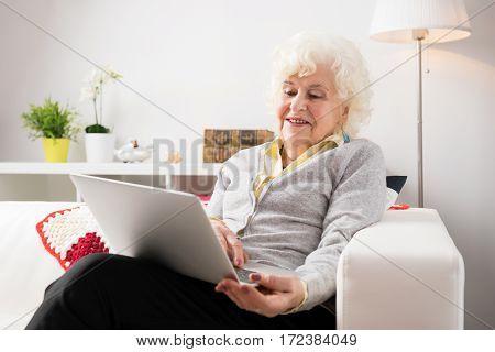 Elderly woman using laptop computer in living room