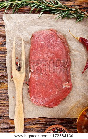 Fresh raw beef steak on kraft paper on the kitchen table standing next to rosemary and meat fork