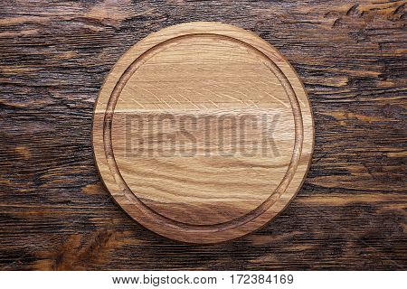 Round wooden cutting board made of oak and ash lies on a brown wooden table. space for text