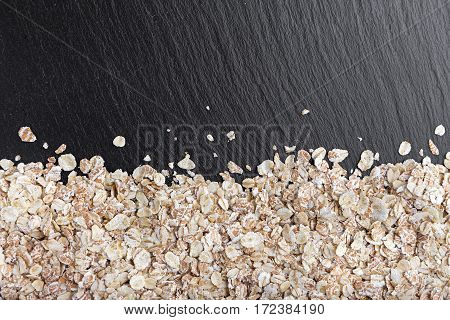 raw oatmeal is scattered on a black background on slate blackboard with space for text