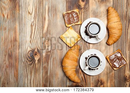 Two Cups Of Coffee, Croissant, Toast And Chocolate On Wooden Table
