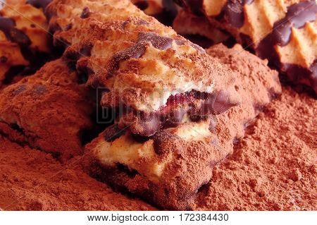 Pile Of Shortbread Cookies With Jam And Chocolate Icing On The Scattered Cocoa Powder