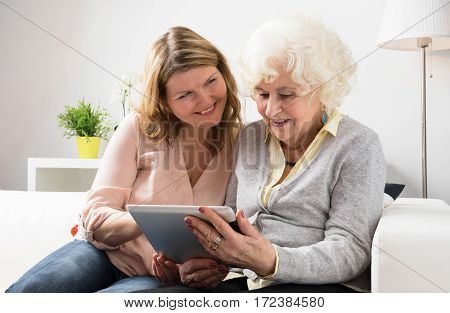 Grandaughter teaching grandmother how to use tablet