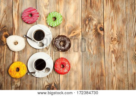 Colorful Donuts And Two Cups Of Coffee On The Wooden Table
