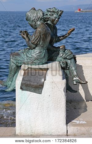 TRIESTE ITALY - OCTOBER 14: Le Sartine Statues in Trieste on OCTOBER 14 2014. Le Sartine Bronze Sculpture One of the Symbols of the City Representing Two Girls Knitting on the Waterfront in Trieste Italy.