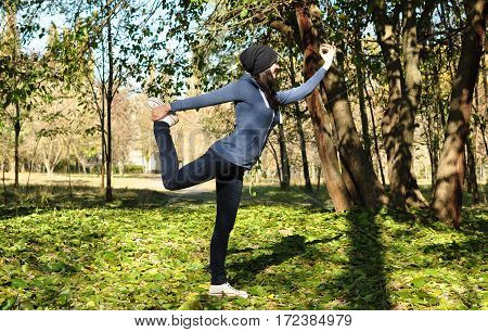 Beautiful Girl Doing Yoga At The Park At A Sunny Day.