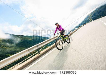 Young Woman Cycling. Shot taken in Switzerland, near Rhone Glacier and Furka Pass.