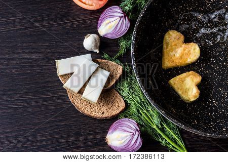 Fried eggs in the shape of a heart in a frying pan near which lay bread slices lard (salo) red onion tomato garlic and dill on dark wooden table