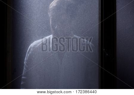 Man Standing Behind Window