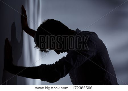 Man Leaning Hands Against Wall