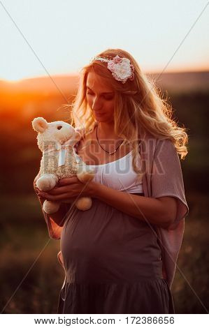 the pregnant girl with a hat in the field of wheat on a sunset