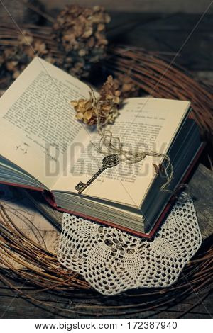 still life in retro style with an old key dry flowers and book.