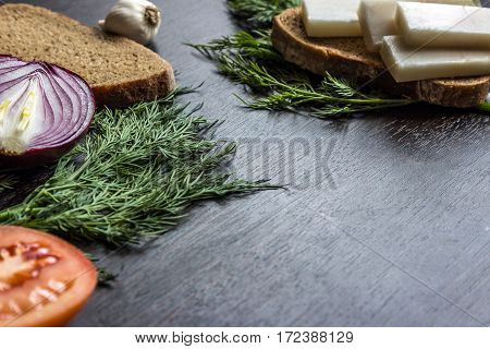 cut red onions tomato dill lard (salo) and garlic on wooden table. Small depth of focus