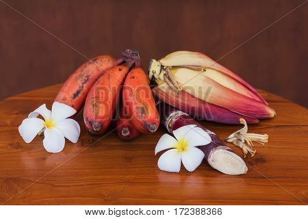 Fresh red banana and unripe banana bunches on wooden table on wooden brown wall