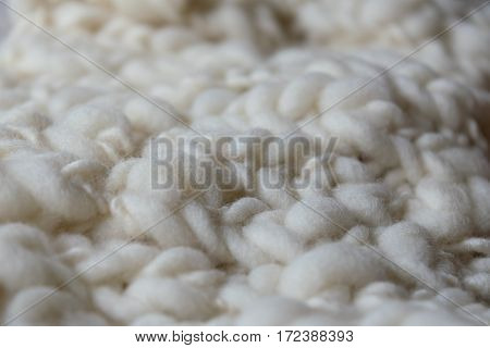White knitted woolen fabric. Closeup. Irregular monochromatic and organic texture.