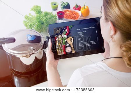 Woman checks the recipe on her tablet.