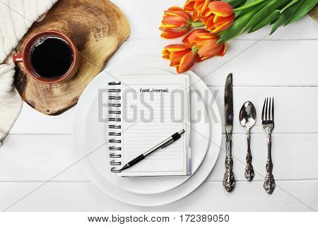 Overhead shot of a food journal over empty plates with a cup of coffee and a bouquet of springtime tulip flowers over white wood table top. Flat lay top view style.
