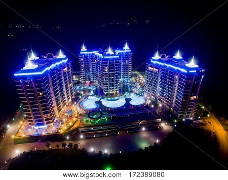 ALANYA, TURKEY - AUG 16, 2015: Three buildings of apartment complex Azura Park Residence with color light at night, aerial photo
